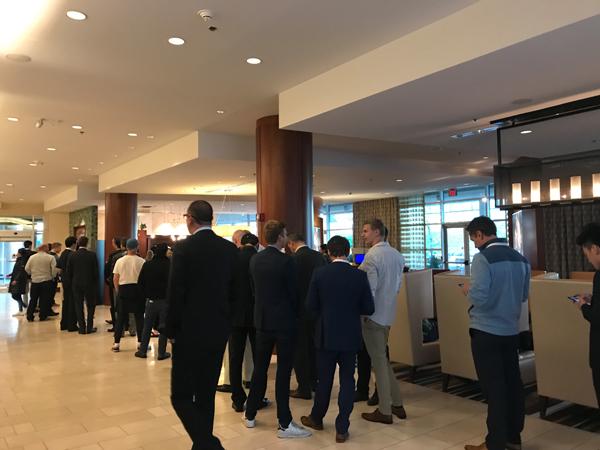 参会股东们在对面酒店排队买咖啡。