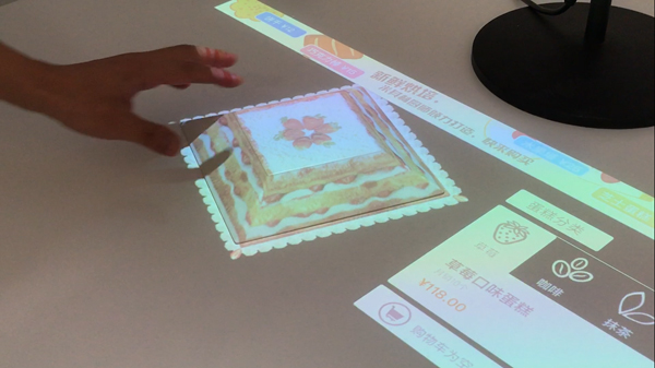 通过网易影见,可以在桌上虚拟演示做蛋糕效果。