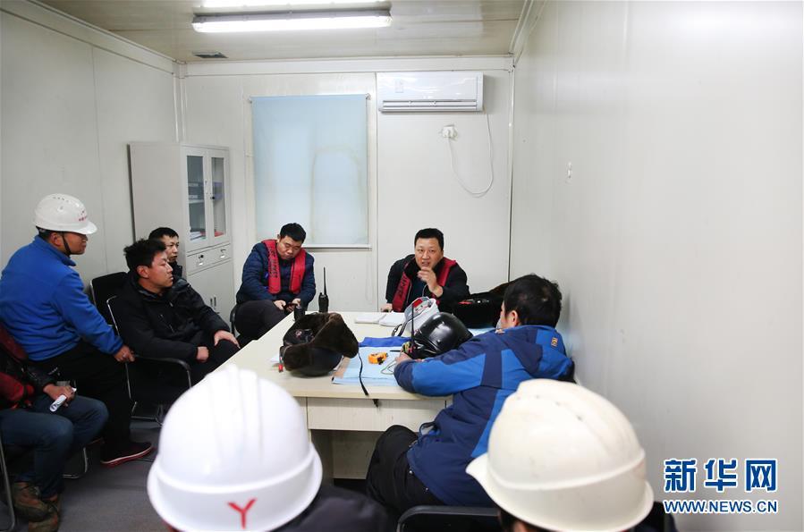 12月28日,顾惠明(右后)和同事在每天一次的例会上钻研当天和近期的做事义务。新华社发(许丛军)