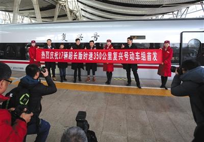 """昨日,乘客与车组人员和超长版""""中兴号""""动车组相符影。新京报记者 王贵彬 摄"""