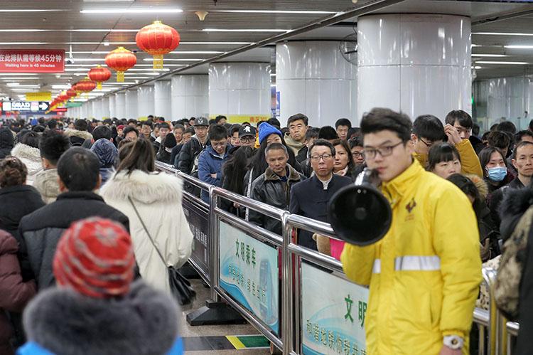 北京西站,地铁事情职员正在开导搭客排队进站搭车。
