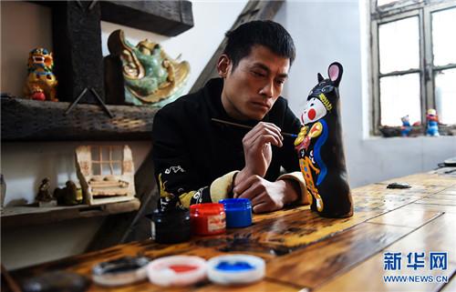 3月5日,河南省浚县杨玘屯村,宋庆春在家中的工作室制作泥咕咕创新作品《瑞鼠献宝》。