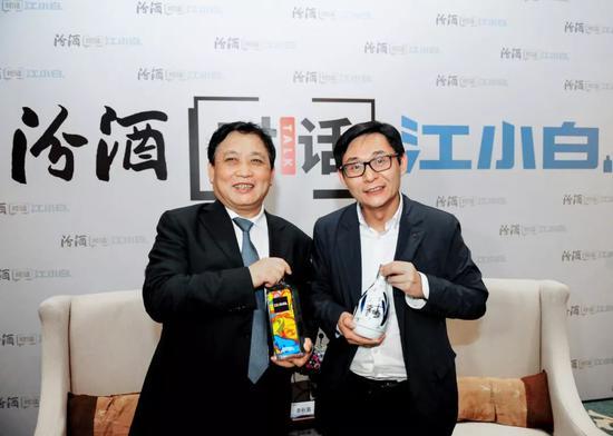 """对话最后,两位企业家相互赠送了自己的产品。李秋喜赠送了一瓶青花汾,而陶石泉则赠送了一瓶""""江小白黑标涂鸦版""""。"""
