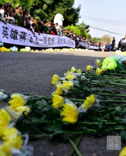 """清晨6时,蒋飞飞的骨灰在其亲属陪伴下离开西昌,踏上回乡路程。与此同时,家乡50万群众从各地纷纷汇聚至英雄""""回家""""沿途,拉起各类白字黑底横幅,列成整齐队伍,含泪迎接烈士归来。"""