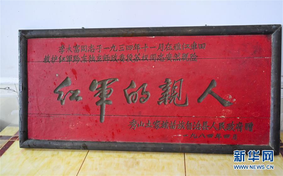 """重庆秀山县雅江镇江西村村民李之文家保存的1984年秀山县人民政府颁发给他父亲李木富的""""红军的亲人""""牌匾(7月18日摄)。 新华社记者 刘潺"""