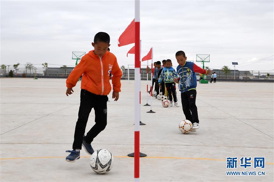 在武威市古浪县黄花滩生态移民区富民新村富民小学,足球兴趣小组的孩子们开展训练(8月22日摄)。新华社记者 范培珅