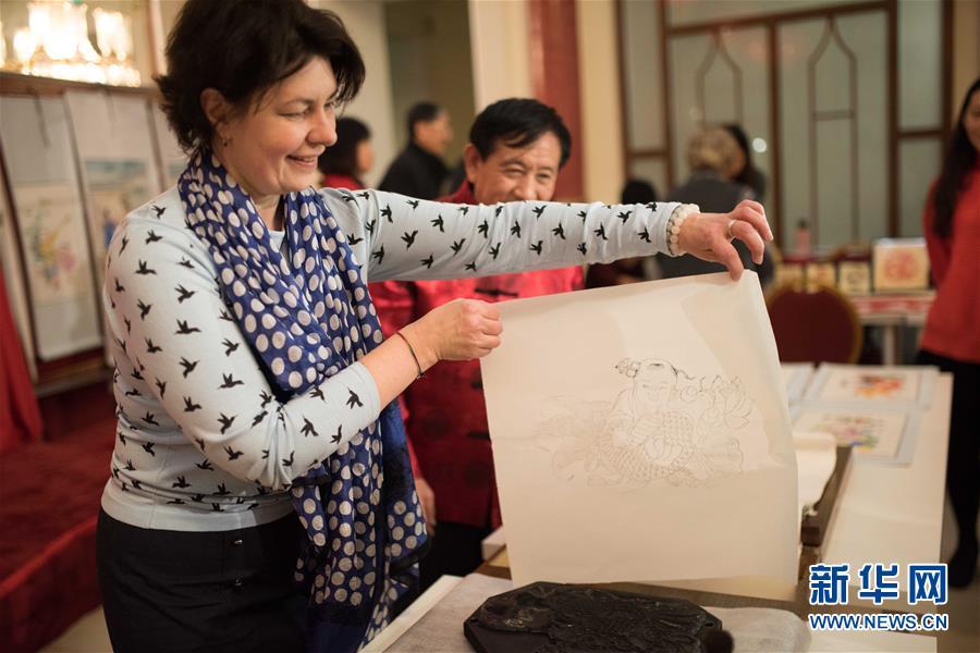 2016年2月1日,在俄罗斯莫斯科中国文化中心,一名女士体验杨柳青木板年画的制作工艺。新华社记者 戴天放