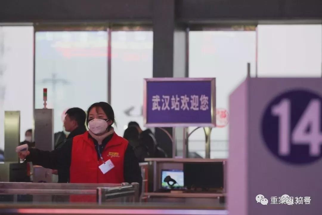 1月21日,武汉火车站,工作人员拿着体温检测仪检测经过进站闸机的体温。摄影/新京报记者 游天�D